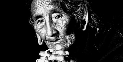 Portrait of elder woman looking into camera, black and white close-up