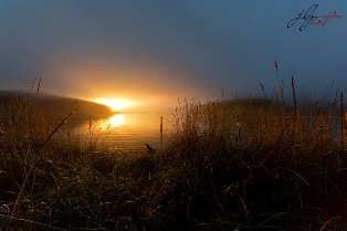 Low key, wide angle shot of water surrounded by marsh and hills at sunrise, a warm yellow sun just at the horizon