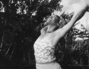 Medium black and white shot of Wyoma in triumphant dance pose, arms up, looking up toward the sky