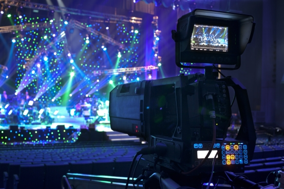 image of television camera in foreground with concert stage in background, coolly lit with numerous lighting units